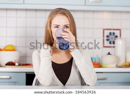 Beautiful caucasian woman sitting in the kitchen and drinking fresh water.