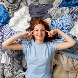 Beautiful caucasian woman smiling and lying down with clutter clothes on the floor. Decluttering pile of messy wardrobe. Cluttered housewife. Fabric. Shopping. Housework idea concept.