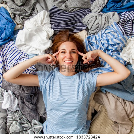 Photo of  Beautiful caucasian woman smiling and lying down with clutter clothes on the floor. Decluttering pile of messy wardrobe. Cluttered housewife. Fabric. Shopping. Housework idea concept.
