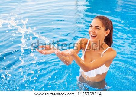 Beautiful caucasian woman splashing water in aquapark