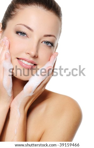Beautiful caucasian woman washing her beauty health face with foam on her hands