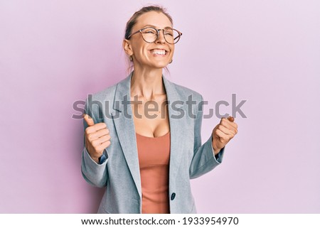 Beautiful caucasian woman wearing business jacket and glasses excited for success with arms raised and eyes closed celebrating victory smiling. winner concept.  Photo stock ©