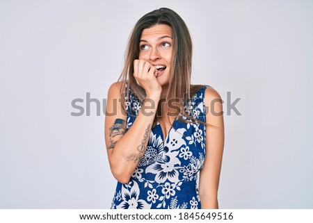 Beautiful caucasian woman wearing casual clothes looking stressed and nervous with hands on mouth biting nails. anxiety problem.  stock photo