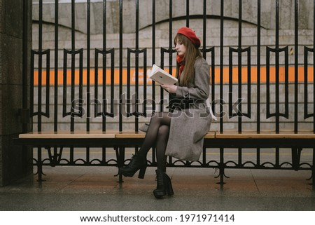 Beautiful Caucasian woman wearing coat, beret and scarf sitting alone on Saint Petersburg metro station reding a book. Image with selective focus and noise effect Foto stock ©