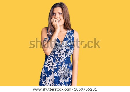 Beautiful caucasian woman wearing summer dress looking stressed and nervous with hands on mouth biting nails. anxiety problem.  stock photo