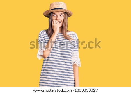 Beautiful caucasian woman wearing summer hat looking stressed and nervous with hands on mouth biting nails. anxiety problem.  stock photo