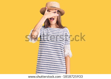 Beautiful caucasian woman wearing summer hat peeking in shock covering face and eyes with hand, looking through fingers with embarrassed expression.  stock photo