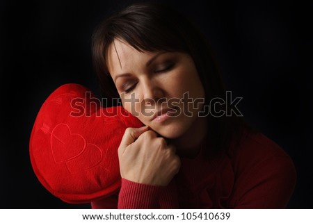 Beautiful Caucasian woman with a happy heart pillow on a dark background