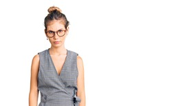 Beautiful caucasian woman with blonde hair wearing business clothes and glasses skeptic and nervous, frowning upset because of problem. negative person.