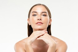 Beautiful Caucasian woman with clean glowing face skin in isolated studio white background for beauty and skin care concepts
