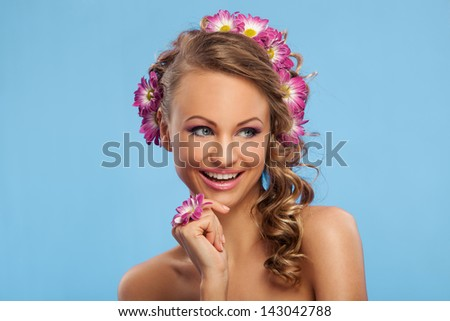 Beautiful caucasian woman with flowers in her hair over blue background