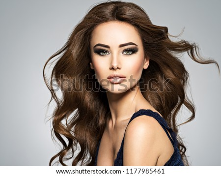 Beautiful caucasian woman with long brown curly hair. Portrait of a pretty young adult girl. Sexy face of an attractive  lady posing at studio over grey background.