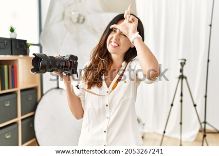 Beautiful caucasian woman working as photographer at photography studio making fun of people with fingers on forehead doing loser gesture mocking and insulting.  Foto stock ©