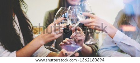 Beautiful caucasian women cheering with glasses of white wine during leisure time in cafe interior, attractive hipster girl saying toast during celebration meeting with friends on publicity area