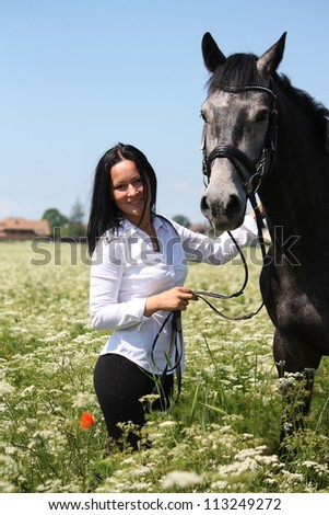 Beautiful caucasian young woman and horse portrait at the field with flowers