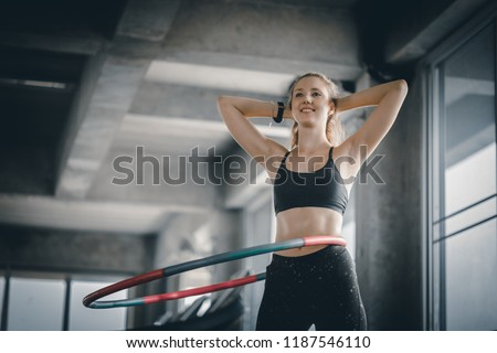 Beautiful caucasian young woman doing hula hoop in step waist hooping forward stance. Young woman doing hula hoop during an exercise class in a gym. Healthy sports lifestyle, Fitness, Healthy concept.