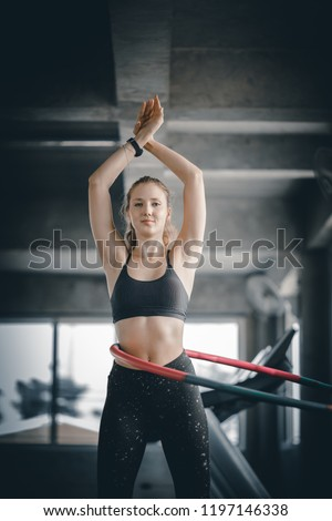 Beautiful caucasian young woman doing hula hoop in step waist hooping forward stance. Young woman doing hula hoop during an exercise class in a gym. Healthy sports lifestyle, Fitness, Healthy concept. #1197146338