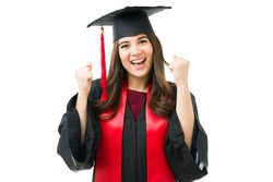 Beautiful caucasian young woman feeling thrilled to receive her bachelor's degree. Female graduate in a gown shouting with excitement during the graduation ceremony