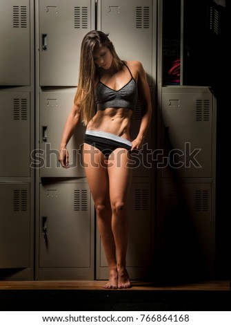 Beautiful caucasian young woman wearing black bikini shorts  and sports bra showing her six pack abs in a dark gym locker room  #766864168