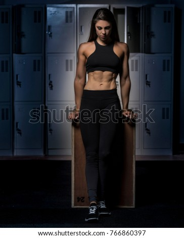 Beautiful caucasian young woman wearing black long tights and sports bra showing her six pack abs posing on a crossfit box in a dark gym locker room  #766860397