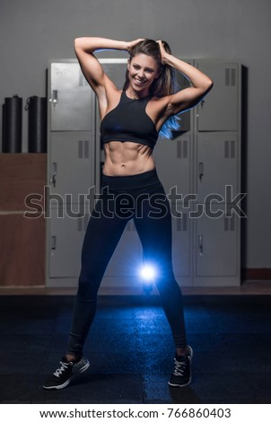 Beautiful caucasian young woman wearing black long tights and sports bra showing her six pack abs posing in a dark gym locker room  #766860403