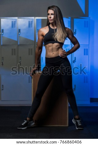 Beautiful caucasian young woman wearing black long tights and sports bra showing her six pack abs posing in a dark gym locker room  #766860406