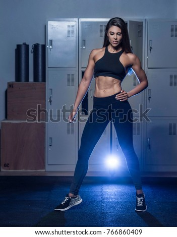 Beautiful caucasian young woman wearing black long tights and sports bra showing her six pack abs posing in a dark gym locker room  #766860409