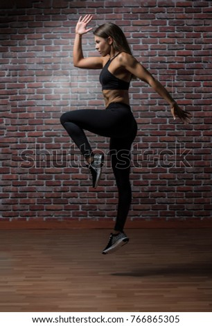 Beautiful caucasian young woman wearing black long tights and sports bra showing her six pack abs with a red brick background performing a sprint leap #766865305
