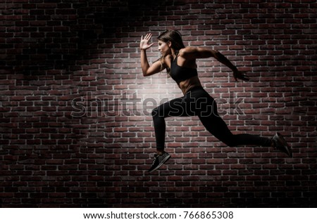 Beautiful caucasian young woman wearing black long tights and sports bra showing her six pack abs with a red brick background performing a sprint leap #766865308