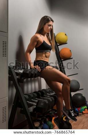 Beautiful caucasian young woman wearing black short  tights and sports bra showing her six pack abs sitting on a rack of dumbbell weights in a gym #766865764