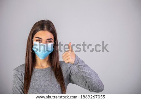 Beautiful caucasian young woman with disposable face mask. Protection versus viruses and infection. Studio portrait, concept with white background. Woman showing thumb up. Foto stock ©