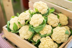 beautiful cauliflower with green leaves in a wooden crate