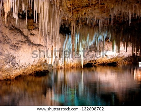 Beautiful cave interior with reflections in clear underground water and lighting