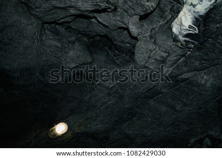 Beautiful cave. View from inside dark dungeon. Textured walls of cave. Background image of underground tunnel. Dampness inside cave. Lighting inside cave for excursions.