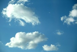 Beautiful celestial landscape with group of white cumulus clouds high in the stratosphere on a sunny summer day