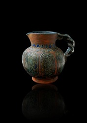 Beautiful ceramic jug with a twisted handle and an intricate design on the body. A pattern of stylised leaves in arched panels. The blues and greens stand out against the red of the terracotta.