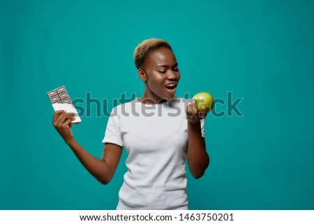 Beautiful, charming african woman holding big green apple and bar of dark chocolate. Handsome, stylish girl in white t shirt posing on blue background, looking at apple, preferring apple. Zdjęcia stock ©