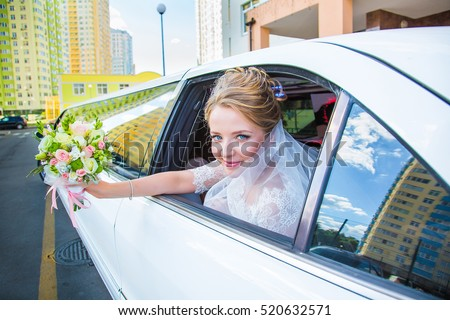 Beautiful, charming bride in wedding dress, waving a bouquet of limousine