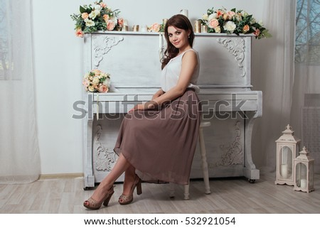 Beautiful charming brunette in the house near the old piano on which lay bouquets of roses. Lots of candles on the piano. Bridesmaid at the wedding. Sexy lady in a nice skirt and blouse #532921054