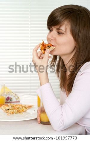 Beautiful charming Caucasian girl eats pizza in the cafe