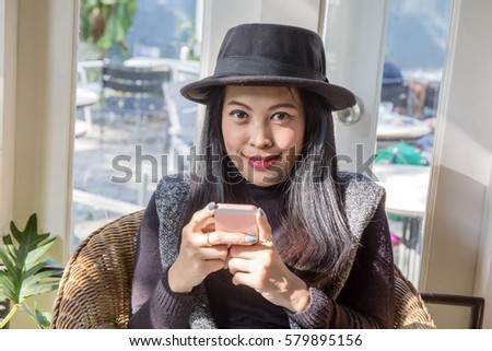 Photo of Beautiful charming tan skin Asian woman sit on wood chair use phone and laptop smiling.Presenting your product. Business woman sit on wooden bench shopping online in coffee shop.