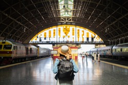 Beautiful charming tourist Asian woman in a white dress with a jean jacket with a sweet straw hat carrying a black backpack at Hua Lamphong Station train station, planning a happy holiday vacation