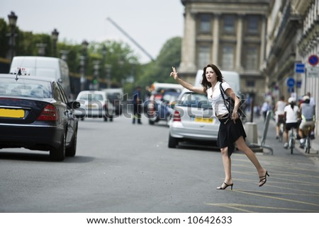 beautiful charming woman hailing a taxi cab in the street of paris france