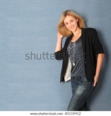 Beautiful charming woman leaning on blue wall