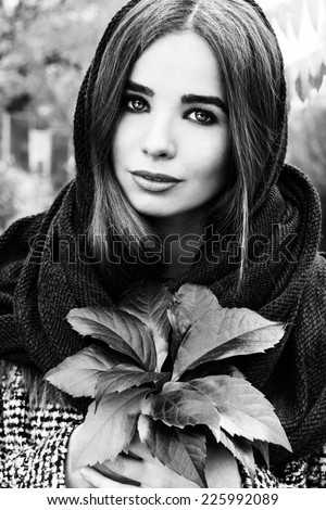 beautiful charming young attractive girl with large blue eyes with a handkerchief on his head, long dark hair holding a fall bouquet of leaves on a cold autumn day