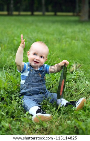 beautiful cheerful boy with record in summer park