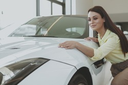 Beautiful cheerful dark haired elegant woman checking out stunning white sportscar at the dealership. Attractive female cusotmer examining car on sale, copy space