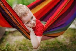 Beautiful cheerful little boy resting in a hammock striped textile