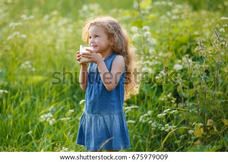 Beautiful cheerful little girl drinking milk #675979009