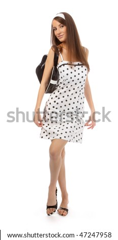 beautiful cheerful model in polka-dot dress with black bag does a slight curtsy